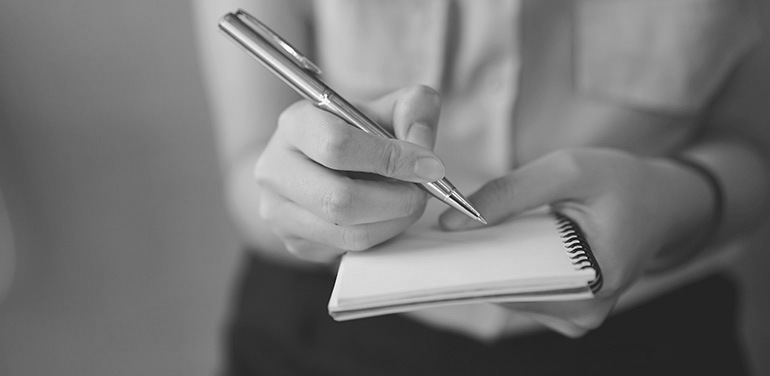 close-up-of-journalist-holding-a-notebook-770